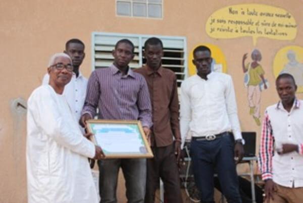 Doudou Fall reçoit un diplôme de remerciements de la part des anciens élèves